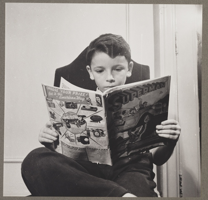 Boy seated and reading Superman comic book